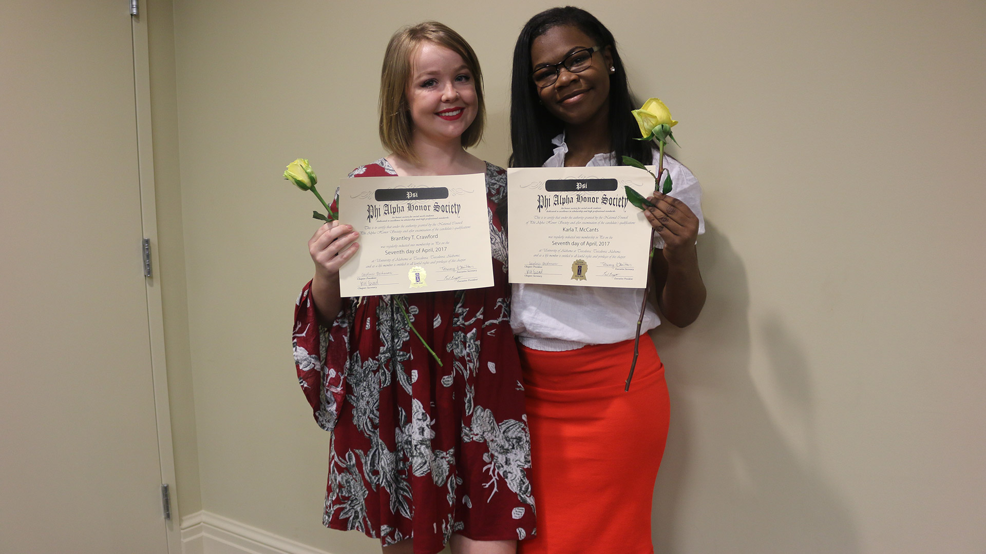 Two girls holding awards