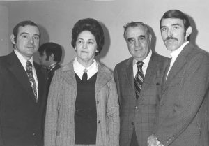 A woman in a cardigan and four guys in suits