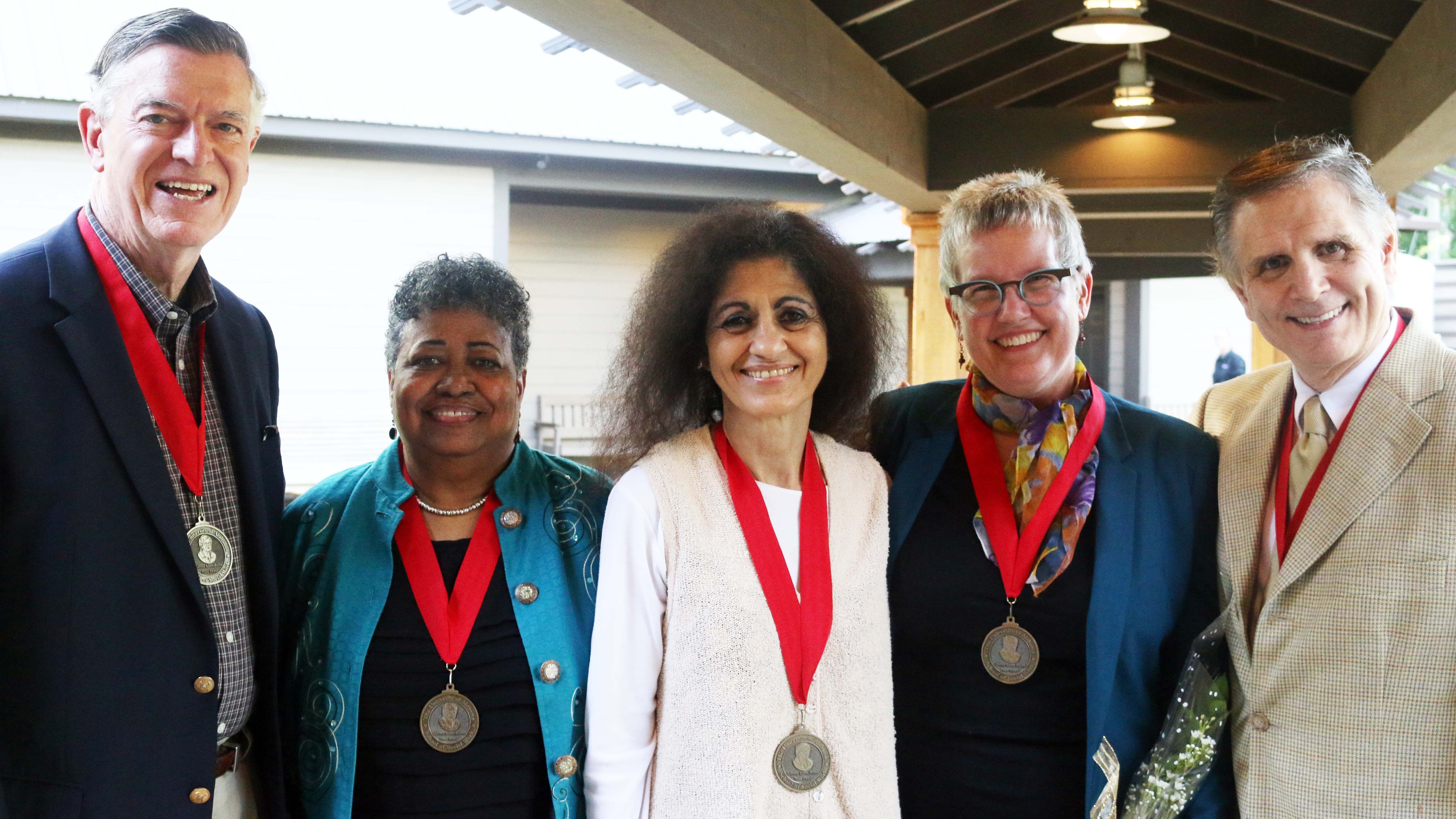 A group of five people with medals around their necks