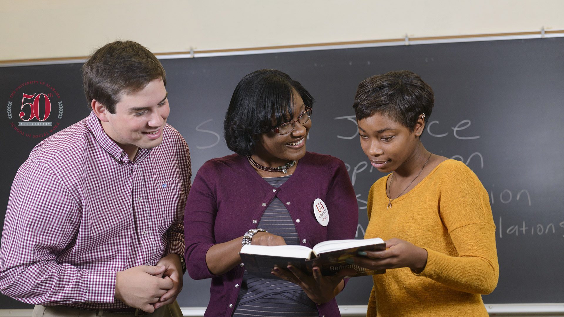 two students with a teacher looking at a book
