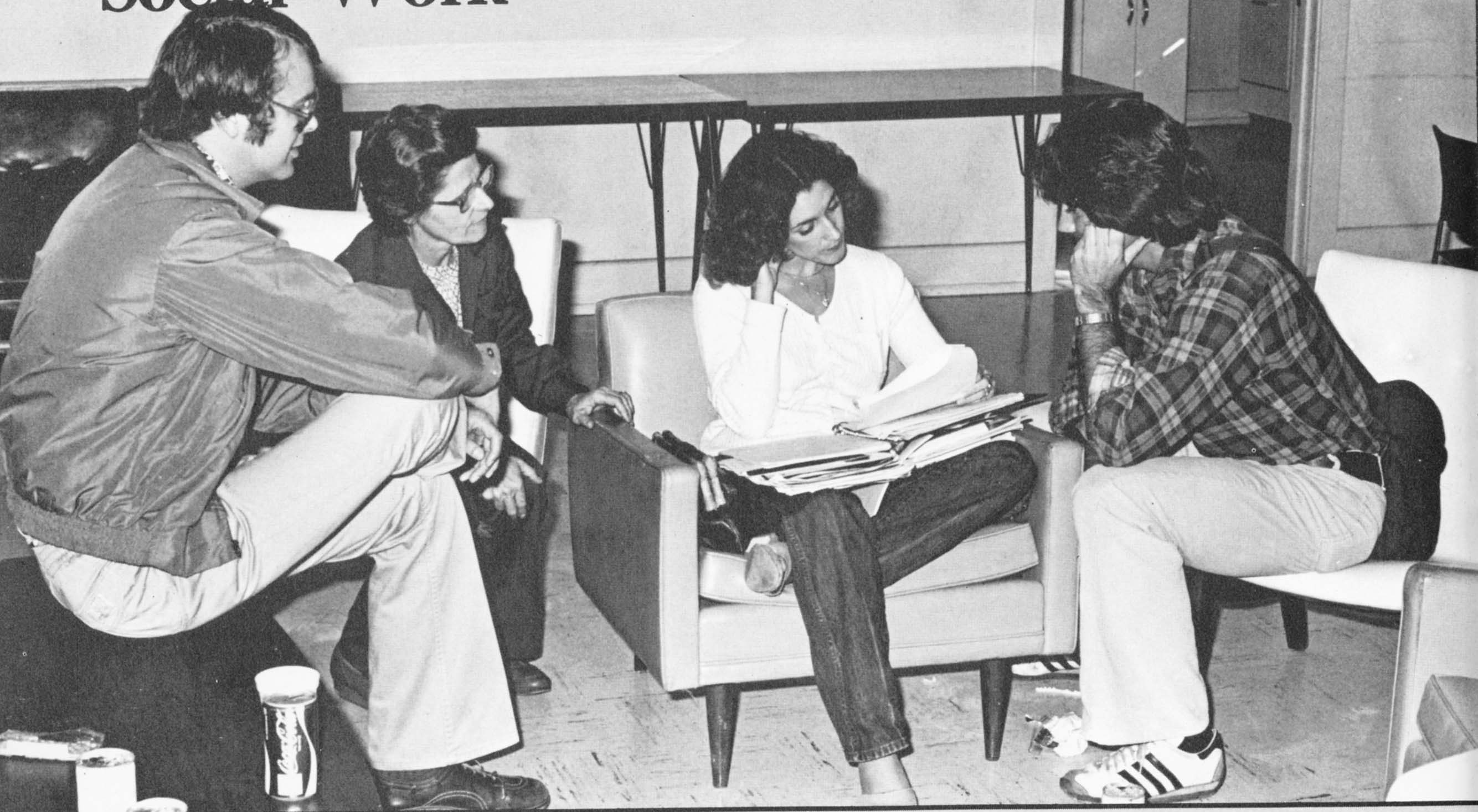 Old black and white photo of people sitting and looking through a binder