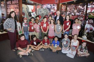 A group of kids doing a class picture pose with Big Al in the Bryant Museum