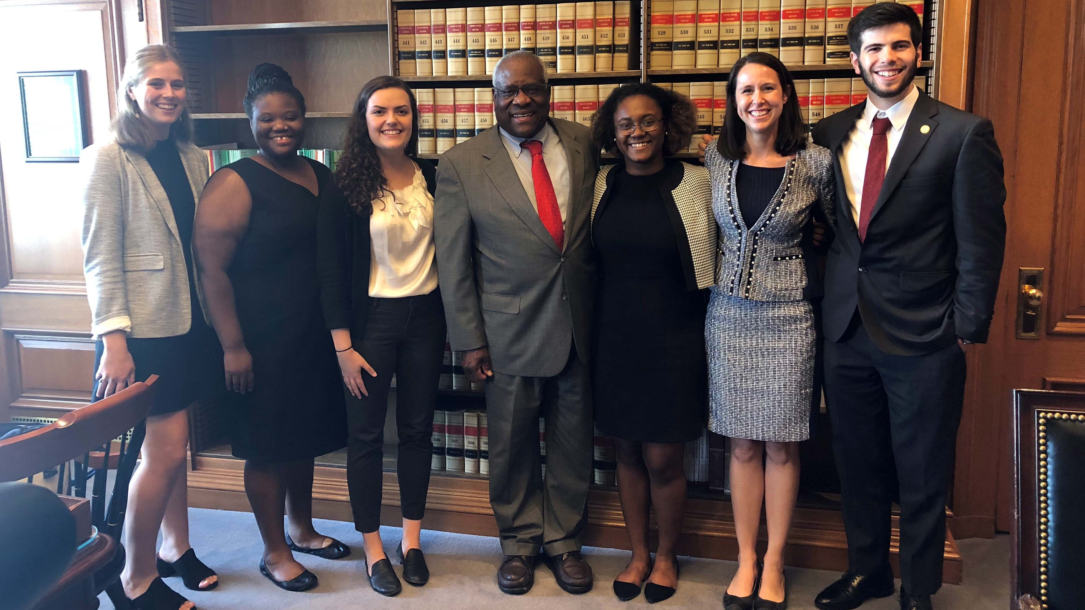 Field Students pose with Justice Clarence Thomas in front of a book case area
