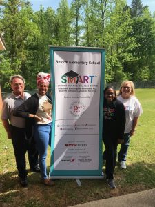Social Work students pose with SMART banner at Reform Elementary School