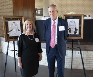 A man and woman pose next to hand-drawn photos of them during a ceremony