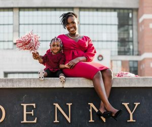 A female university student and her daughter pose for a picture