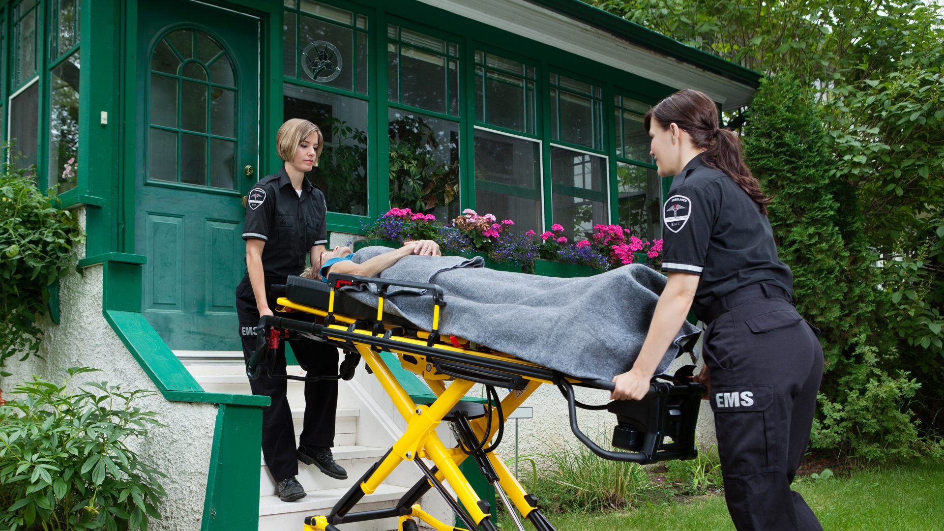 Two female paramedics remove an elderly woman from a home.