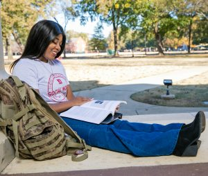 A female university student studies in front of a campus building.