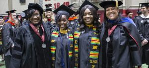 Recent female master's degree graduates pose for a photo