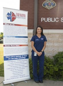 A female social worker poses near a promotional banner