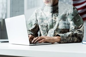 A male military member works a laptop computer