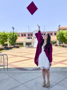 A white female student tosses a mortar board into the air