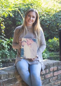 A white woman holds a canvas portrait while posing for a photo outdoors