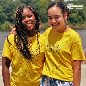 Two black females pose for a picture outdoors